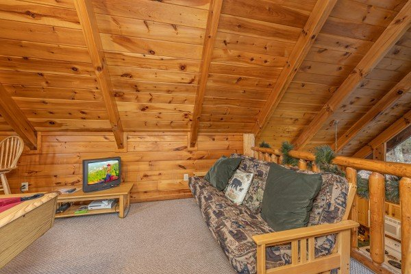 Loft with a futon and TV at A Lover's Secret, a 1 bedroom cabin rental located in Gatlinburg