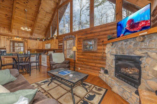 Living room with fireplace and TV attached to a dining space and kitchen at A Lover's Secret, a 1 bedroom cabin rental located in Gatlinburg