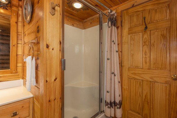 Shower next to a jacuzzi tub at A Lover's Secret, a 1 bedroom cabin rental located in Gatlinburg
