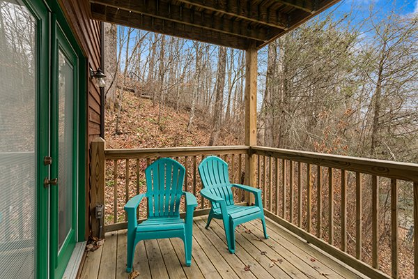 Adirondack chairs on a covered deck at Omg! A 2 bedroom cabin rental located in Gatlinburg