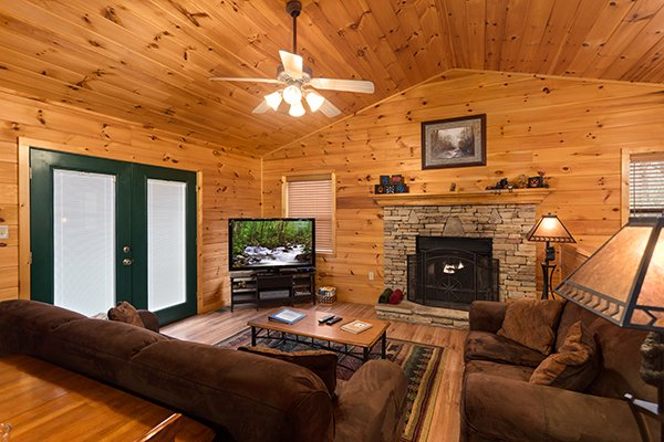 Living room with fireplace and TV at Omg! A 2 bedroom cabin rental located in Gatlinburg