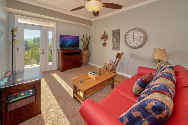 Living room with TV, arcade game, and balcony access at River Dreamin', a 2 bedroom cabin rental located in Pigeon Forge