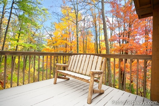 Log framed bench seat surrounded by fall foliage at Hooked on Bears, a 2 bedroom cabin rental located in Pigeon Forge