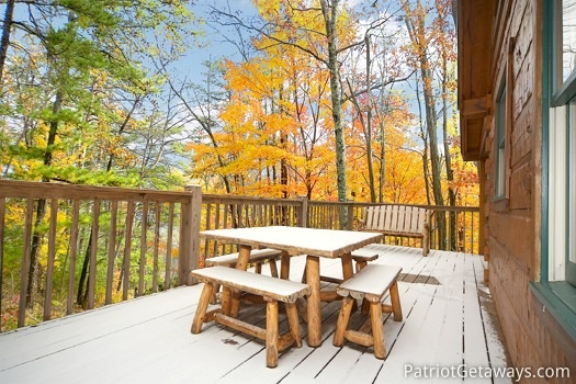 Log framed patio table on the deck at Hooked on Bears, a 2 bedroom cabin rental located in Pigeon Forge