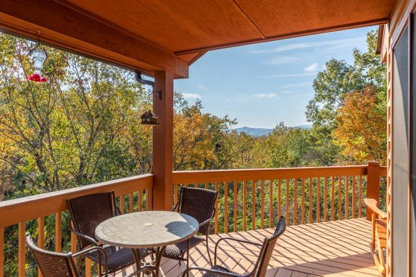 Covered deck with dining table for four at Lazy Bear Retreat, a 4 bedroom cabin rental located in Pigeon Forge