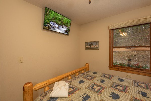 Bedroom with a wall mounted TV at Lazy Bear Retreat, a 4 bedroom cabin rental located in Pigeon Forge