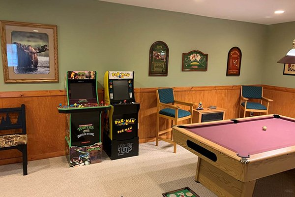 Two arcade games, electric fireplace, and pool table in the game room at Lazy Bear Retreat