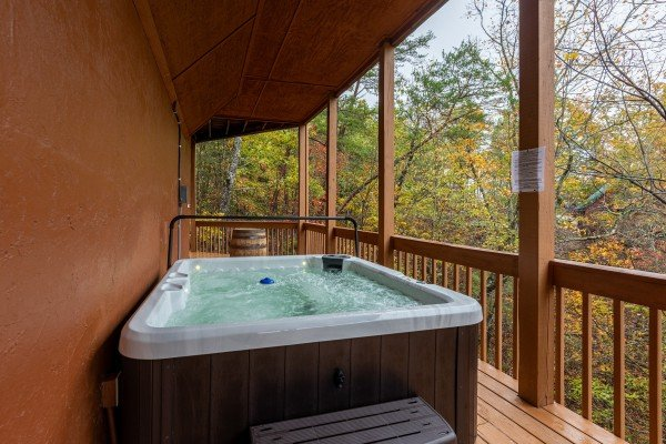 Hot tub on a covered deck at Lazy Bear Retreat, a 4 bedroom cabin rental located in Pigeon Forge