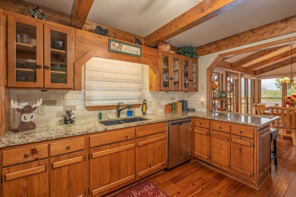 Kitchen with granite counters and breakfast bar at Lazy Bear Retreat, a 4 bedroom cabin rental located in Pigeon Forge