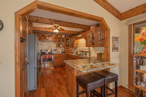 Breakfast bar seating for two and kitchen with stainless appliances at Lazy Bear Retreat, a 4 bedroom cabin rental located in Pigeon Forge
