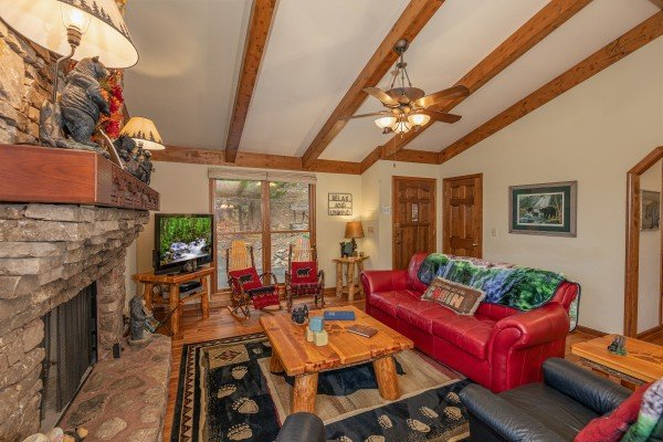 Living room with fireplace, TV, and red sofa at Lazy Bear Retreat, a 4 bedroom cabin rental located in Pigeon Forge