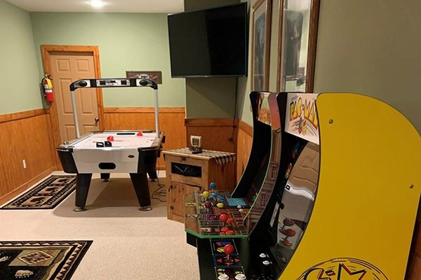 Air hockey, two arcade games, and a TV in the game room at Lazy Bear Retreat