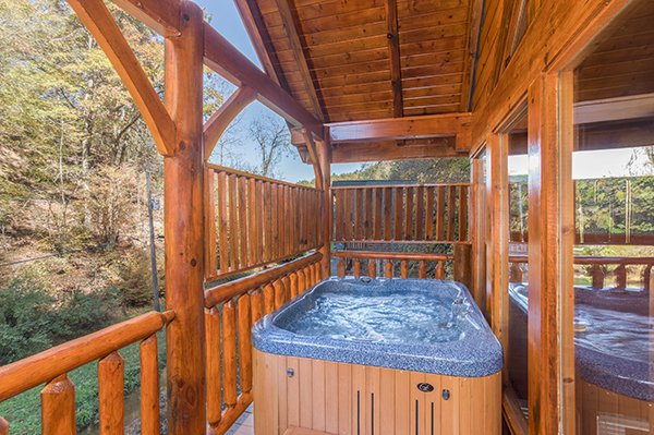 Hot tub on the covered porch at Smokey Max Cabin, a 2 bedroom cabin rental located in Pigeon Forge