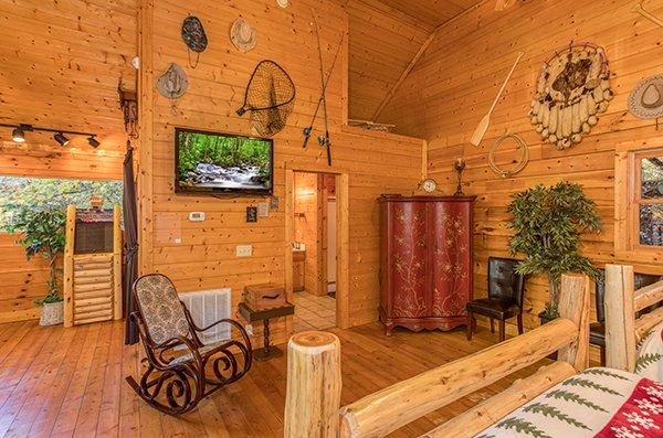 Rocking chair and TV in the loft bedroom at Smokey Max Cabin, a 2 bedroom cabin rental located in Pigeon Forge