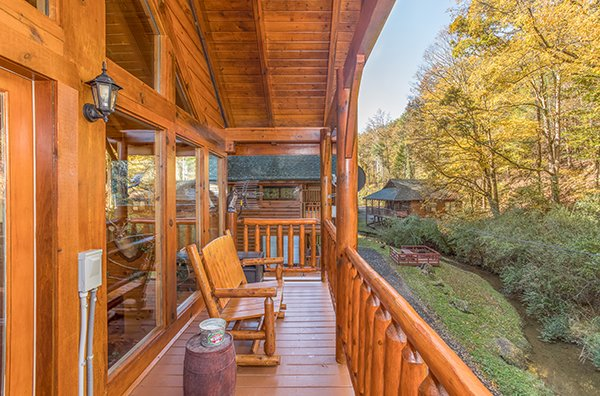 Upper deck with log rocker at Smokey Max Cabin, a 2 bedroom cabin rental located in Pigeon Forge