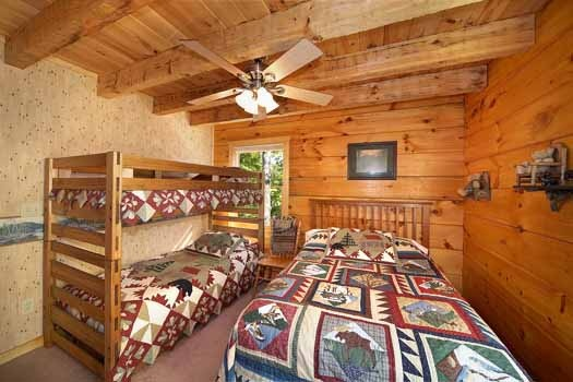 Bedroom with twin bunk beds next to a full sized bed at Eagle's Loft, a 2-bedroom cabin rental located in Pigeon Forge