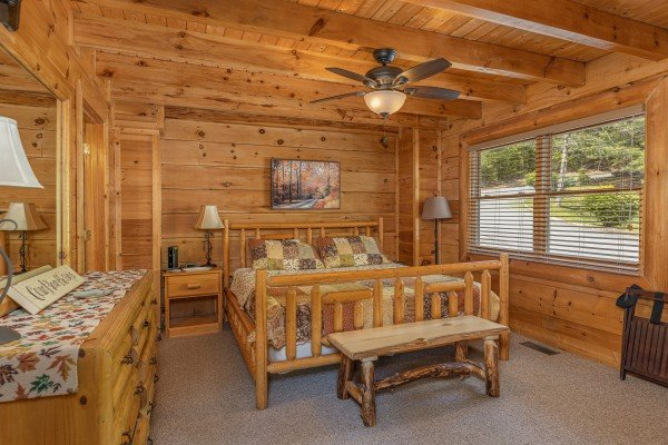 First bedroom with a log bed, two night stands, dresser, and bench at Autumn Blessings, a 2 bedroom cabin rental located in Pigeon Forge