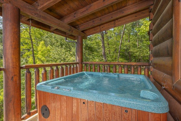 Hot tub on a covered deck at Autumn Blessings, a 2 bedroom cabin rental located in Pigeon Forge