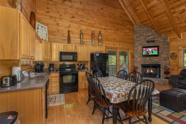Dining table for six in a kitchen with black appliances at Autumn Blessings, a 2 bedroom cabin rental located in Pigeon Forge