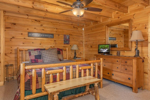 Bedroom with a log bed, night stand, dresser, TV, and bench at Autumn Blessings, a 2 bedroom cabin rental located in Pigeon Forge
