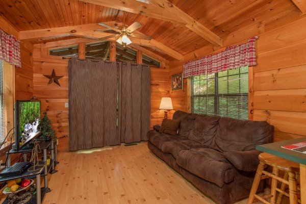 living room with couch and television at angel's dream a 1 bedroom cabin rental located in gatlinburg