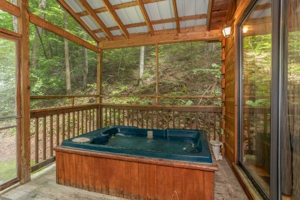 hot tub on a screened in porch at angel's dream a 1 bedroom cabin rental located in gatlinburg