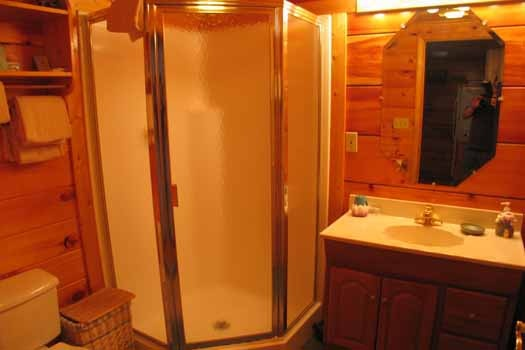 Bathroom with shower in the corner at Just Us, a 1 bedroom cabin rental located in Pigeon Forge