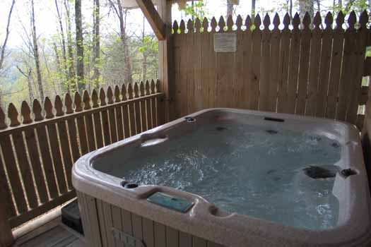 Hot tub on the deck with privacy fence at Just Us, a 1 bedroom cabin rental located in Pigeon Forge