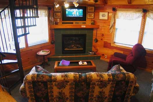 living room with fireplace at just us a 1 bedroom cabin rental located in pigeon forge