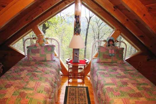 lofted bedroom with two twin beds at just us a 1 bedroom cabin rental located in pigeon forge