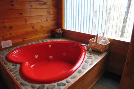 Red heart shaped jacuzzi tub in private room at Just Us, a 1 bedroom cabin rental located in Pigeon Forge