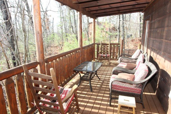 Covered back deck with lots of seating at Ivy Lodge, a 1 bedroom cabin rental located in Pigeon Forge