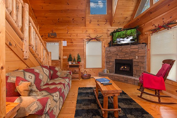 Stone fireplace and TV in the living room at Ivy Lodge, a 1 bedroom cabin rental located in Pigeon Forge