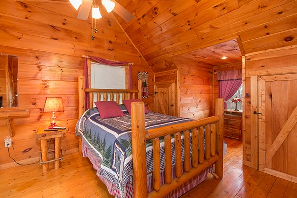 Queen sized log bed in the loft space at Ivy Lodge, a 1 bedroom cabin rental located in Pigeon Forge