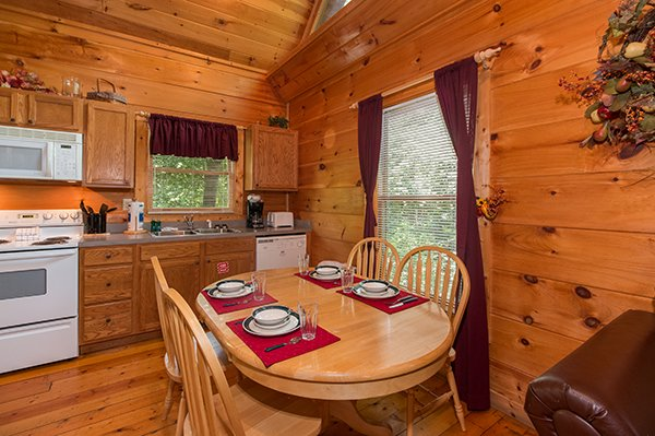 Dining space for four and a kitchen with white appliances at Fallin' in Love, a 1-bedroom cabin rental located in Gatlinburg