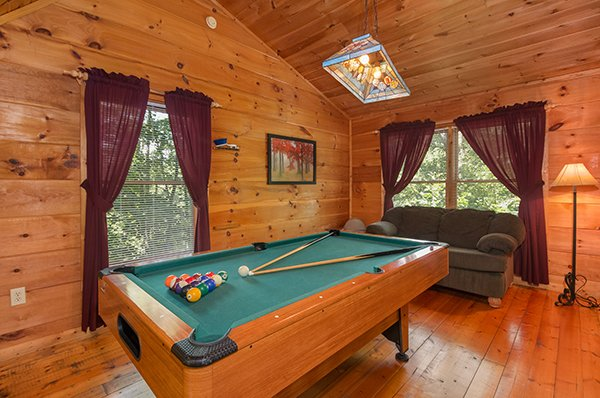 Green felted pool table and a sofa in the game loft at Fallin' in Love, a 1-bedroom cabin rental located in Gatlinburg