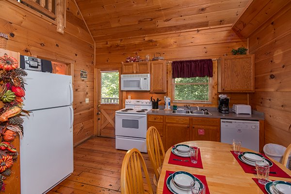 Kitchen with white appliances at Fallin' in Love, a 1-bedroom cabin rental located in Gatlinburg