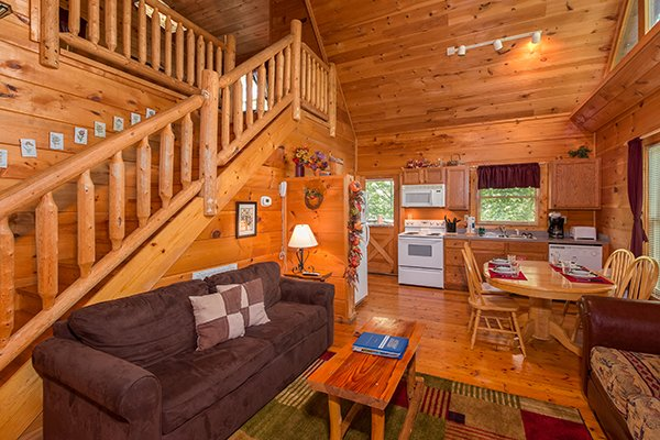 Looking through the living room, into the dining space and kitchen at Fallin' in Love, a 1-bedroom cabin rental located in Gatlinburg