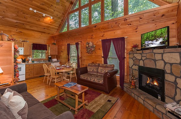 Open concept living, dining, and kitchen with a fireplace, TV, and loft windows at Fallin' in Love, a 1-bedroom cabin rental located in Gatlinburg