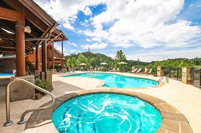 Resort outdoor pool and spa at Hibernation Hideaway #745, a 2-bedroom Pigeon Forge cabin rental