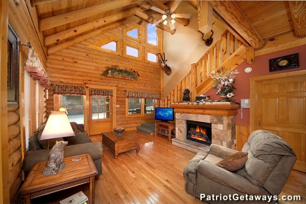 Living room with vaulted ceiling, fireplace, and high windows at Hibernation Hideaway #745, a 2-bedroom cabin rental located in Pigeon Forge