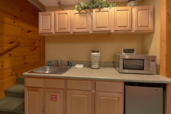 Kitchenette with a small fridge and microwave in the basement bedroom at HIbernation Hideaway #745, a 2-bedroom Pigeon Forge cabin rental