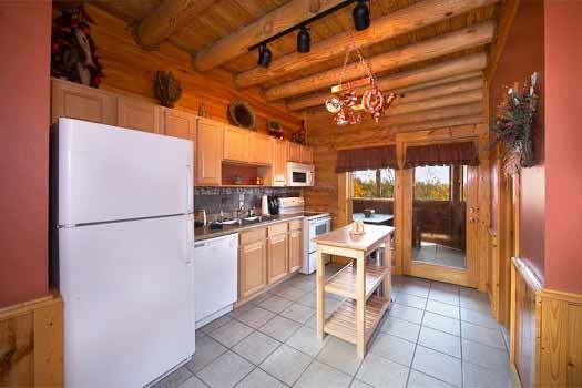 White appliances in the kitchen at Hibernation Hideaway #745, a 2-bedroom cabin rental located in Pigeon Forge