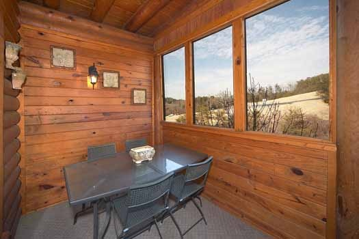 Dining table for four on screened deck at Hibernation Hideaway #745, a 2-bedroom Pigeon Forge cabin rental