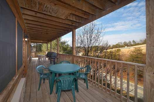Patio table and chairs on shared deck at Hibernation Hideaway #745, a 2-bedroom Pigeon Forge cabin rental