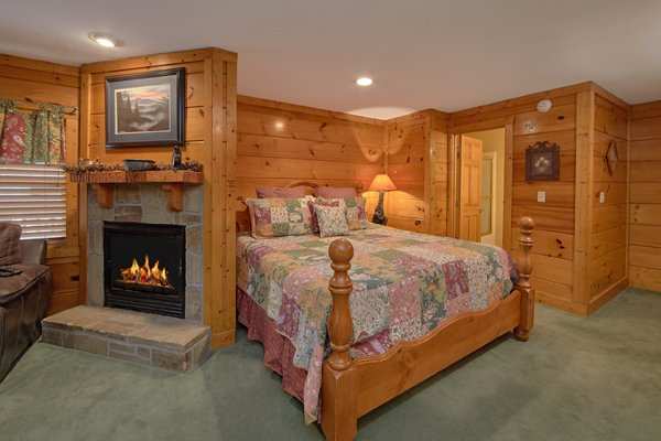 King bed and fireplace in the basement bedroom at Hibernation Hideaway #745, a 2-bedroom cabin rental located in Pigeon Forge