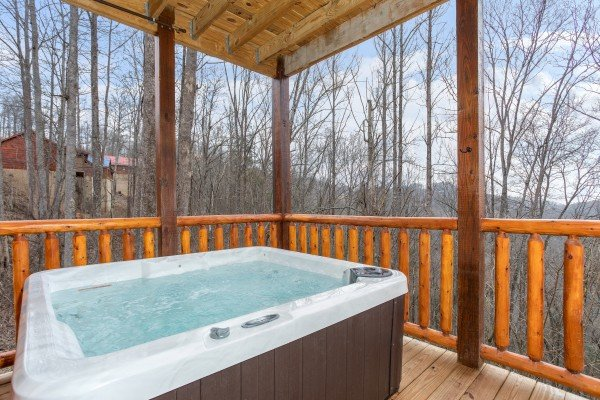 Hot tub on a covered deck at Happy Bear's Hideaway, a 2 bedroom cabin rental located in Gatlinburg