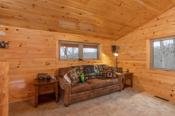 Queen sleeper sofa in the living room at Happy Bear's Hideaway, a 2 bedroom cabin rental located in Gatlinburg