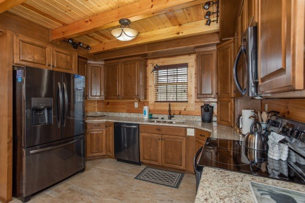 Kitchen with granite counters and grey appliances at Moonlight Inn Gatlinburg, a 2 bedroom cabin rental located in Gatlinburg
