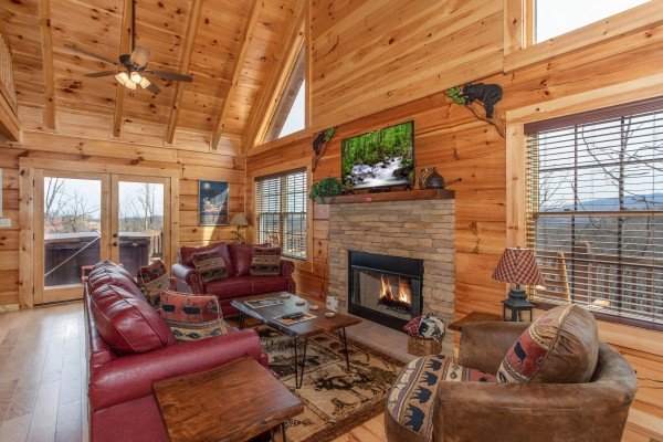 Living room with fireplace, TV, and seating at Moonlight Inn Gatlinburg, a 2 bedroom cabin rental located in Gatlinburg
